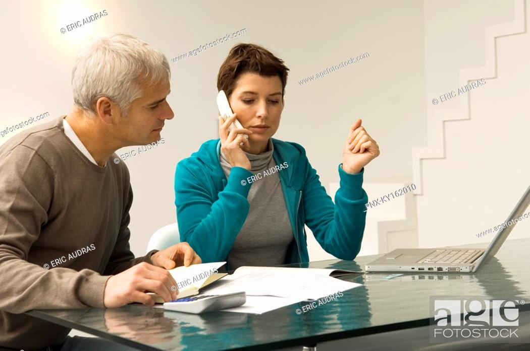 Stock Photo: Mature man calculating bills and a mid adult woman talking on a mobile phone beside him.