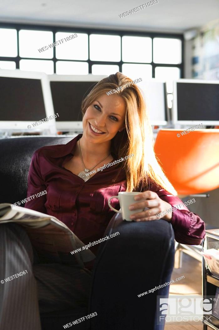 Stock Photo: Businesswoman in office holding cup and newspaper , portrait.