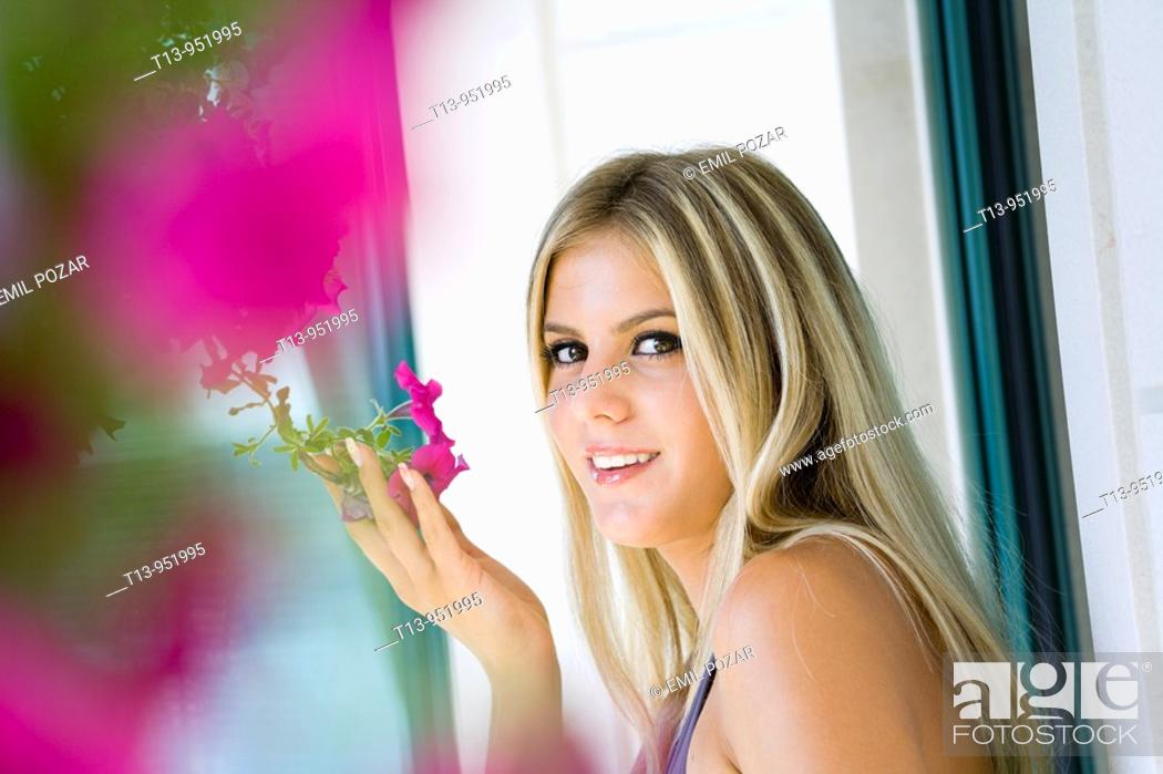 Stock Photo: Attractive young woman is smelling a flower.