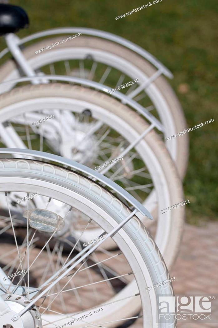 Stock Photo: Nice looking white bicycles parked on the city for rental.