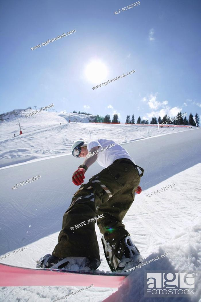 Stock Photo: Snowboarder Riding a Half-Pipe.
