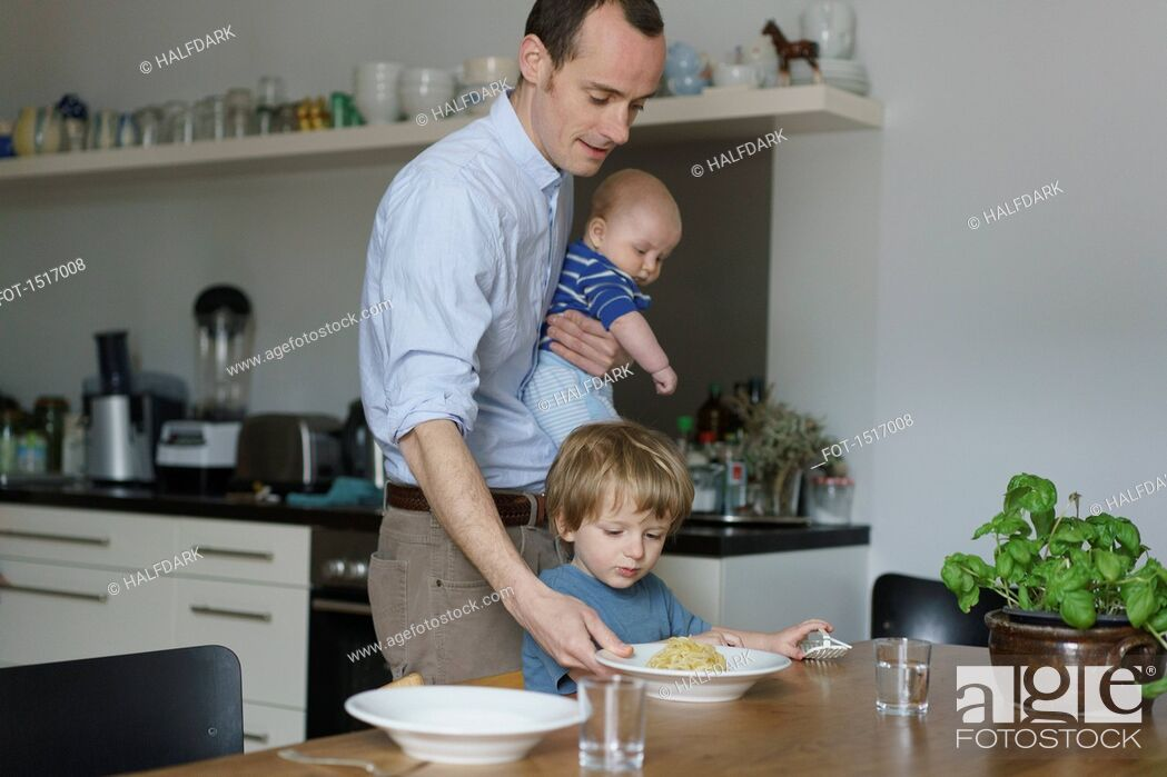 Stock Photo: Father carrying toddler while giving food to son at dining table.