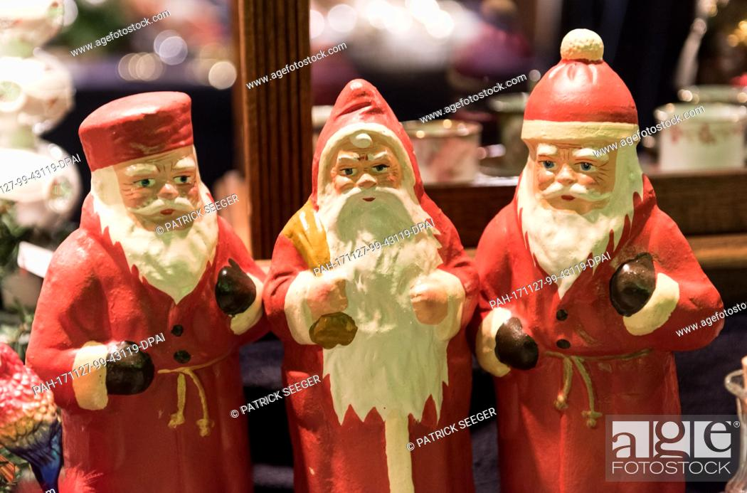 Stock Photo: Three figures of Father Christmas are displayed at a stand at the Christmas market in Freiburg, Germany, 27 November 2017.