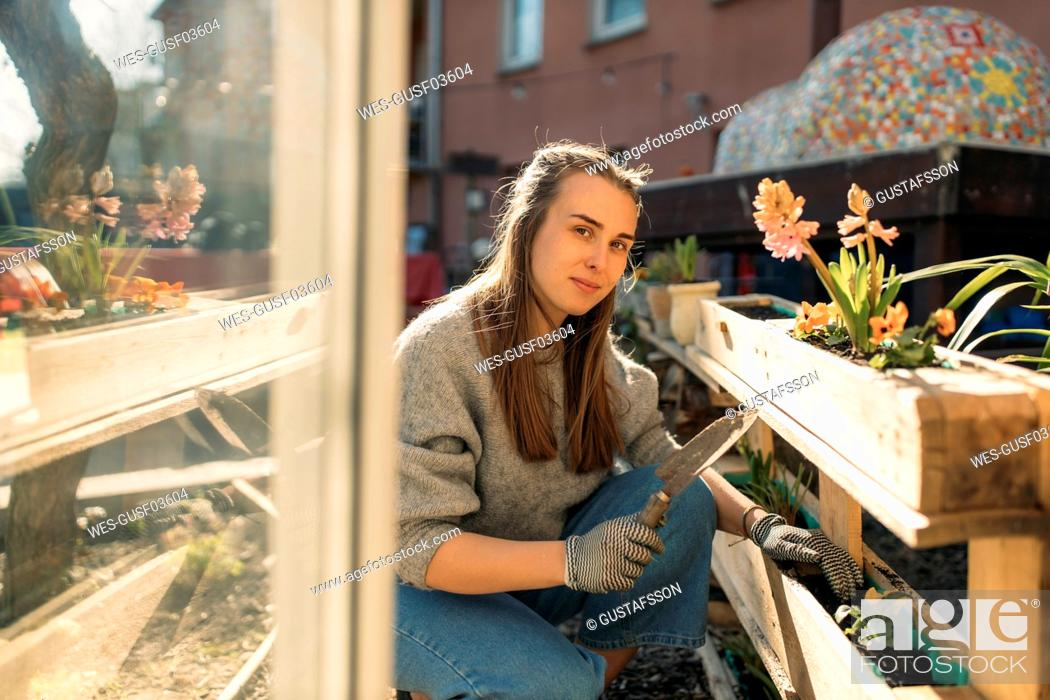 Stock Photo: Portrait of young woman working in garden in sunshine.