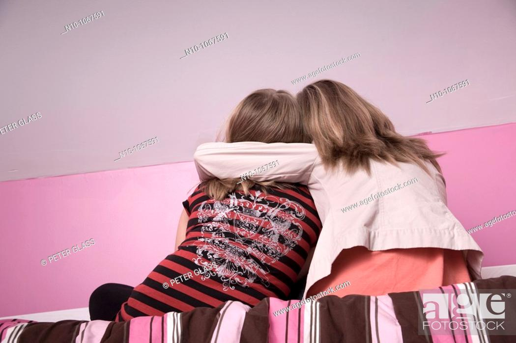 Stock Photo: Blond preteen sisters on a bed.