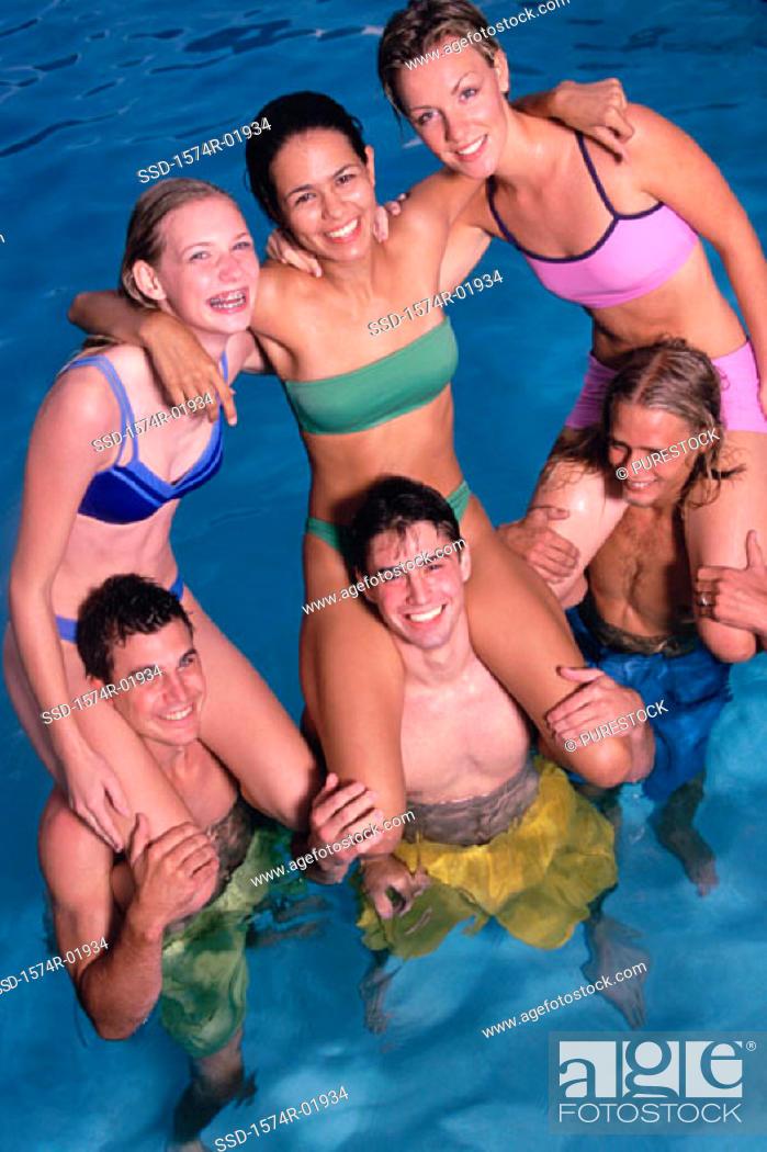 Stock Photo: Group of teenage girls sitting on teenage boys shoulders in the water.