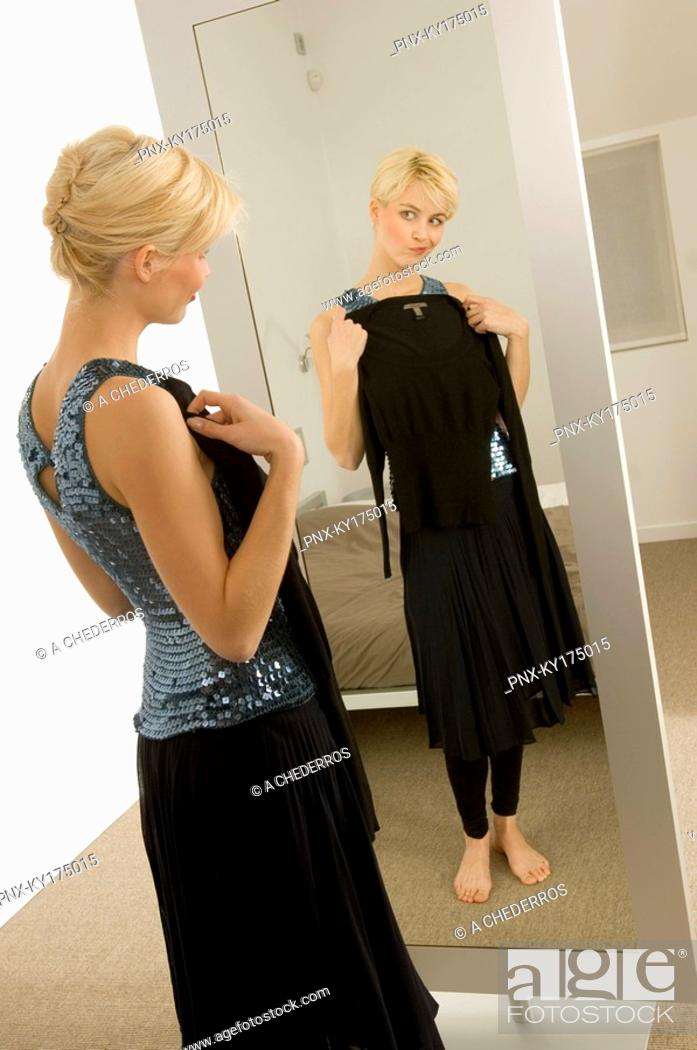 Stock Photo: Young woman trying on a dress in front of a mirror.