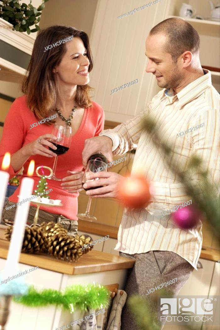 Stock Photo: Couple drinking red wine in the kitchen.
