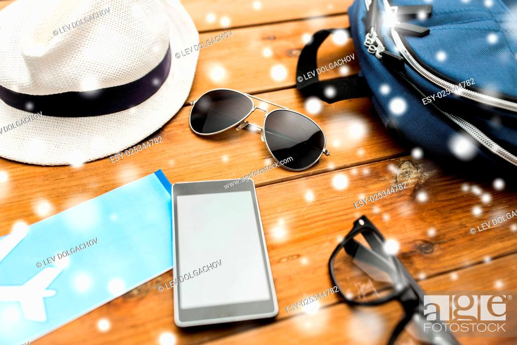 Stock Photo: travel, tourism, technology and winter holidays concept - smartphone, airplane ticket and traveler personal stuff over snow.