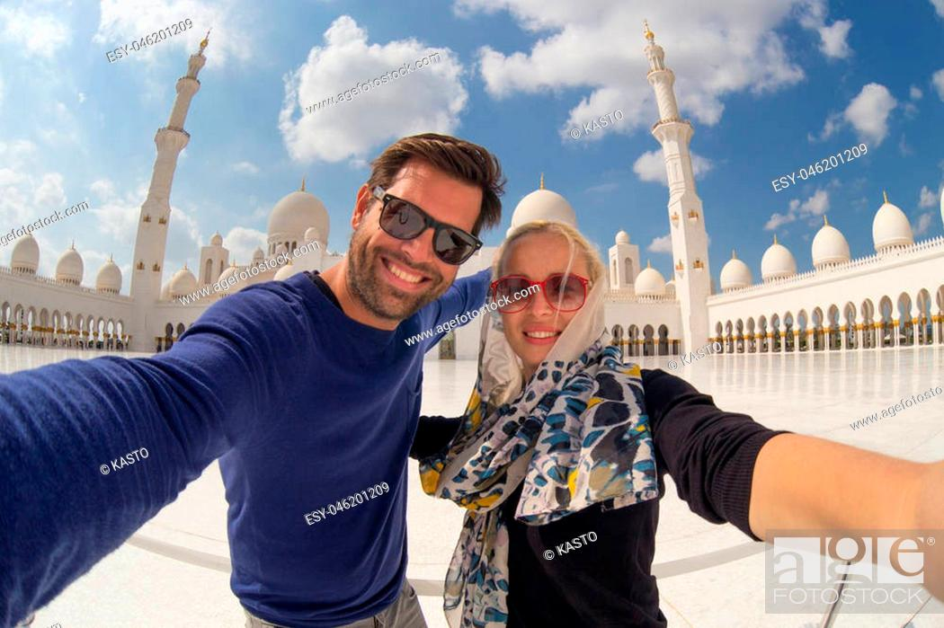 Stock Photo: Tourist couple taking selfie in the courtyard of famous Sheikh Zayed Grand Mosque in Abu Dhabi, United Arab Emirates.
