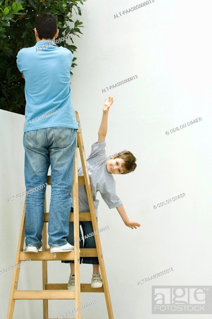 Stock Photo: Father and son standing on ladder, boy pretending to be a plane.