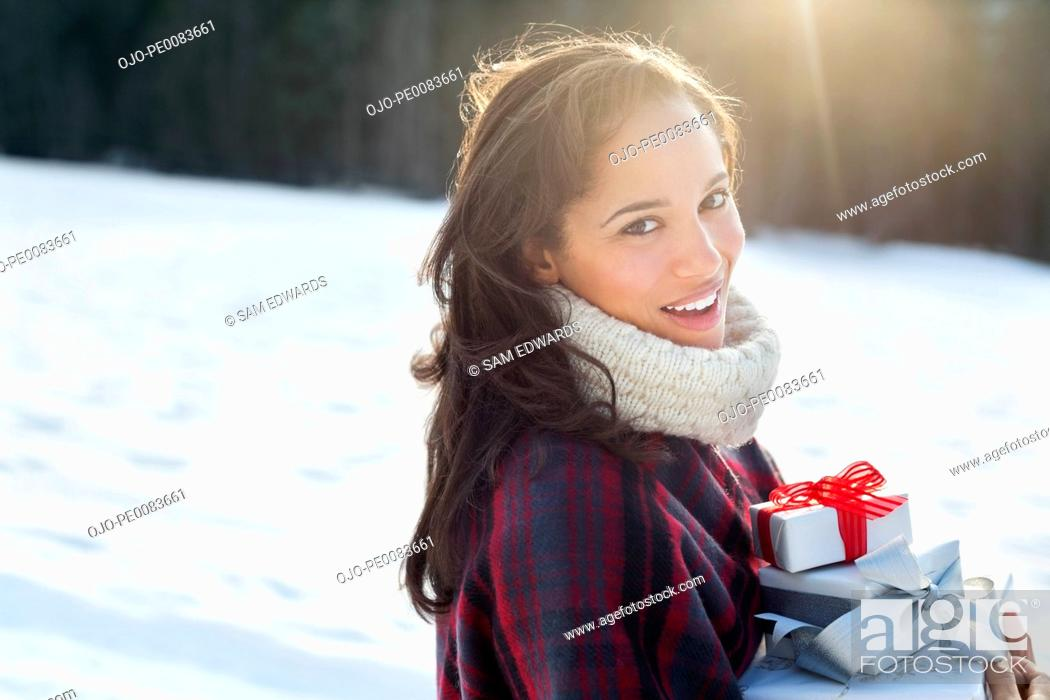 Stock Photo: Portrait of smiling woman holding Christmas gifts in snow.
