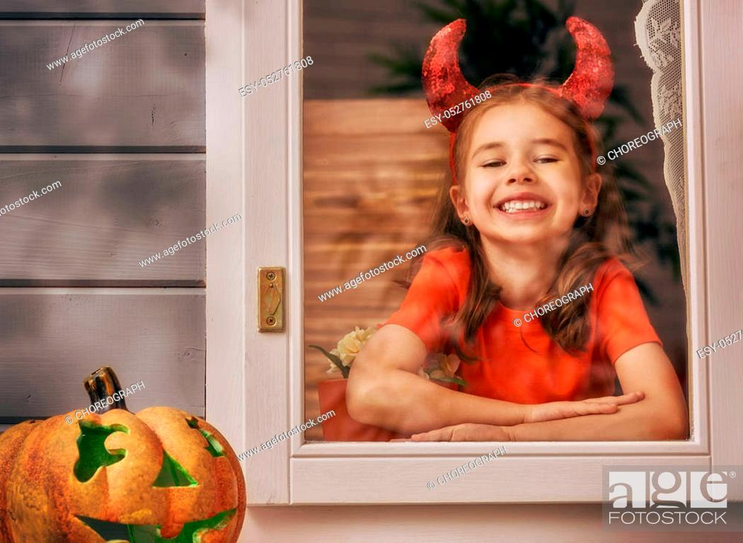 Stock Photo: Happy Halloween! Cute cheerful kid looking on the window. Beautiful child girl in devil costume in the house decorated to Halloween.