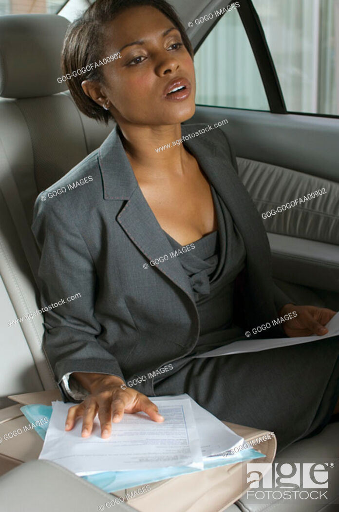 Stock Photo: Businesswoman straining to see from backseat.