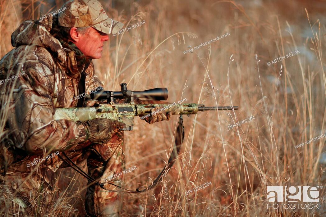 Stock Photo: Predator Hunter Stalking In A Field With A Rifle.