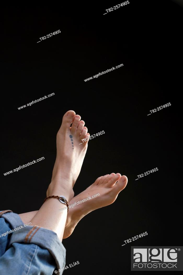 Stock Photo: feet of young woman on black background.