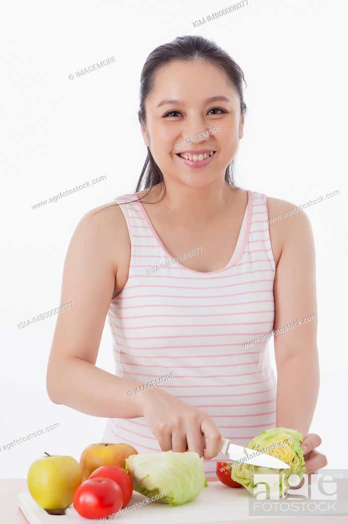 Imagen: Pregnant woman cutting vegetables and smiling at the camera,.