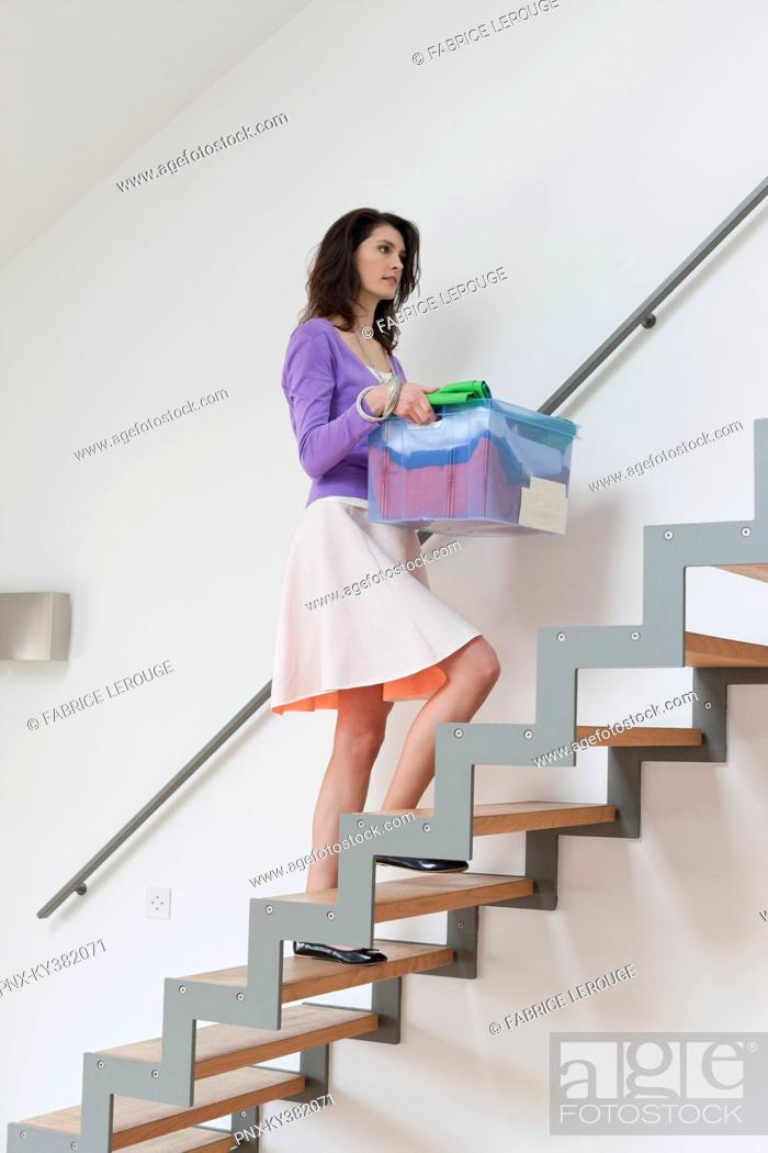 Stock Photo: Woman carrying a box of clothes.