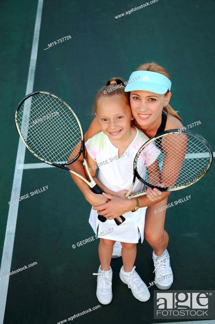 Stock Photo: Mother and daughter posing with tennis rackets.