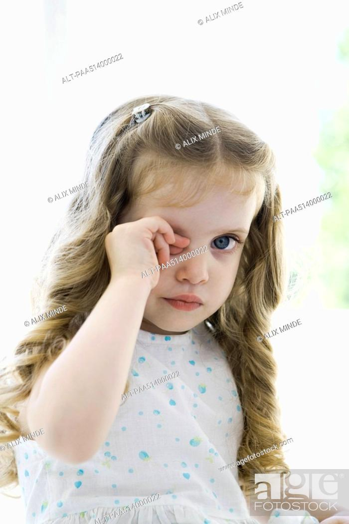 Stock Photo: Little girl rubbing her eye, looking at camera.