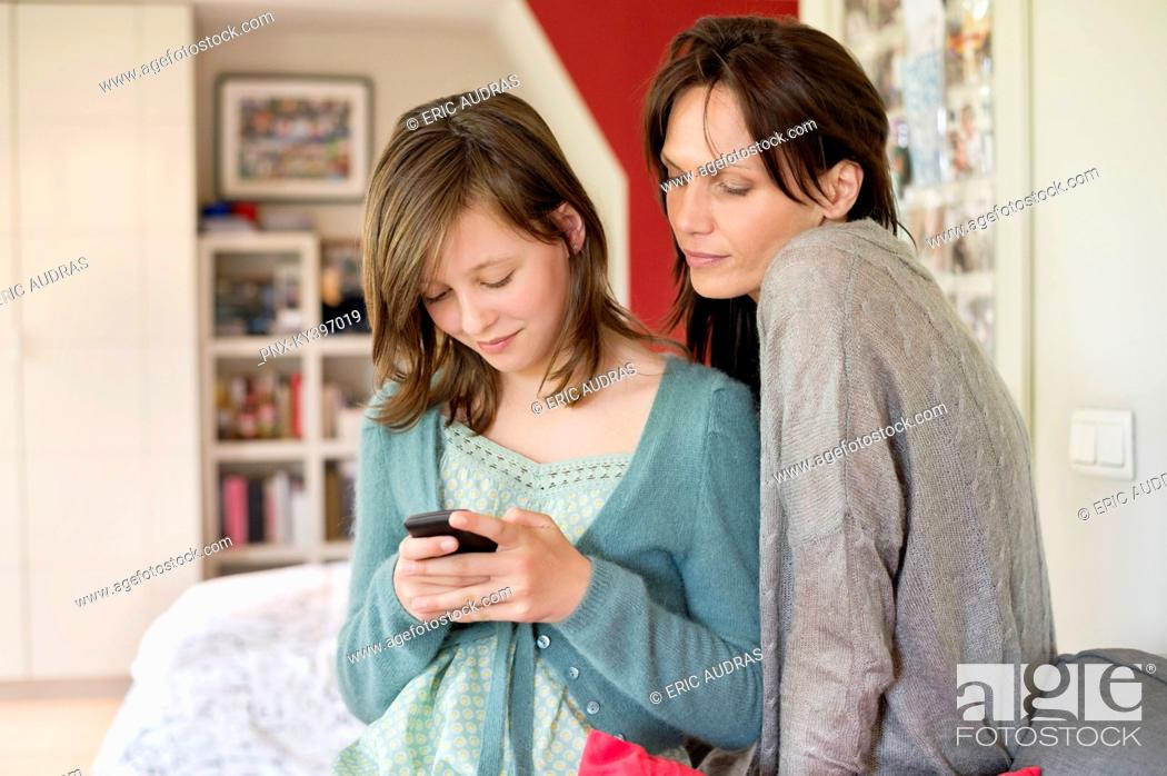 Stock Photo: Girl text messaging on mobile phone with her mother at home.