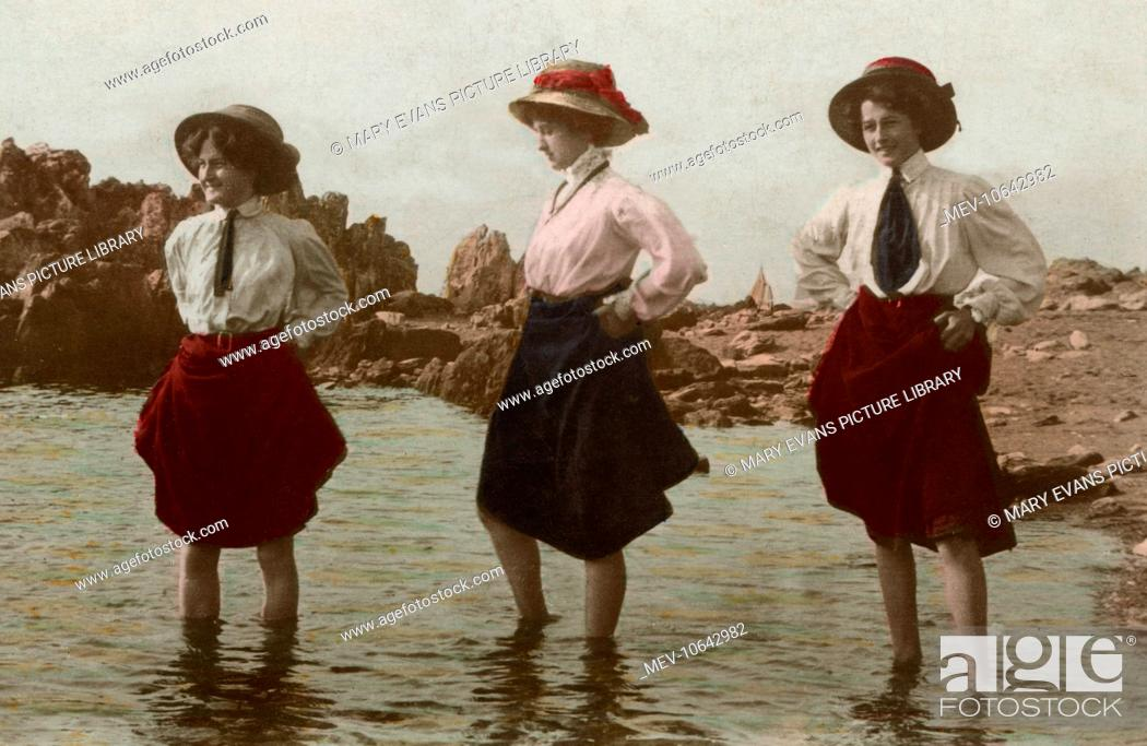 Stock Photo: Three women hitch up their skirts and take a paddle at the seaside.