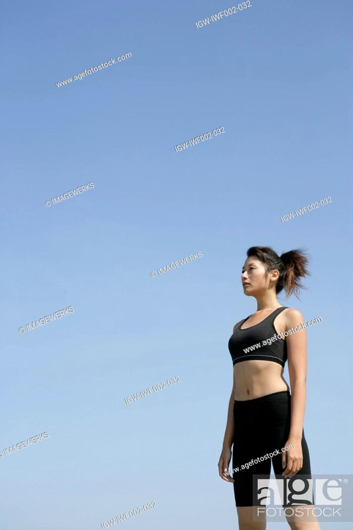 Stock Photo: A side view of a woman in workout suit seen under the sky.
