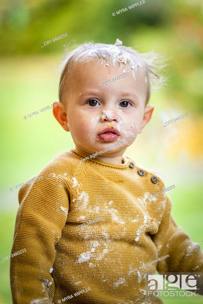 Stock Photo: Baby boy having fun on his one year birthday, smashing a birthday cake.