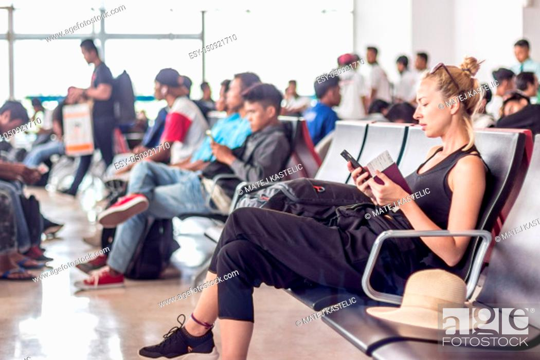 Stock Photo: Casual sporty young blond female traveler using her cell phone while waiting to board a plane at the departure gates at the asian airport terminal.