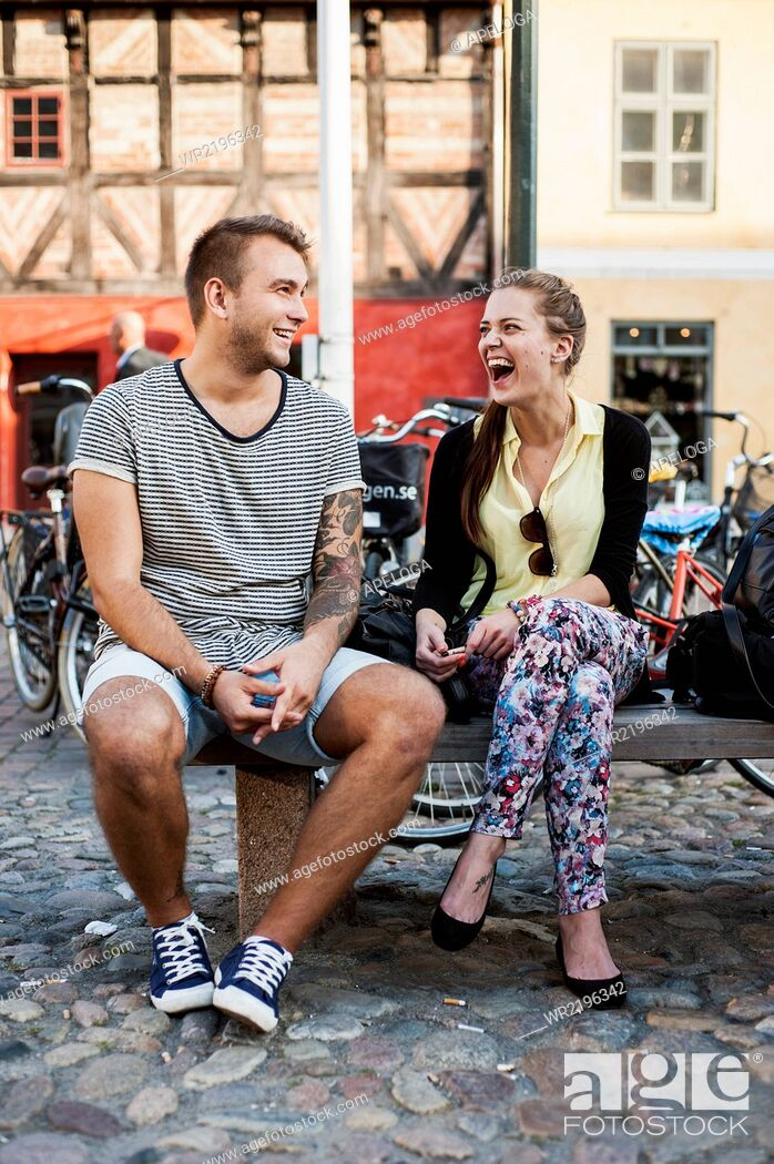 Stock Photo: Full length of young friends laughing while sitting on bench in city.