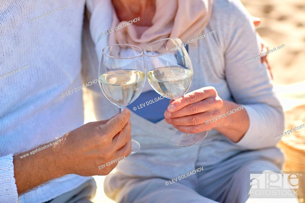 Stock Photo: family, age, holidays, leisure and people concept - close up of happy senior couple having picnic and clinking wine glasses on summer beach.