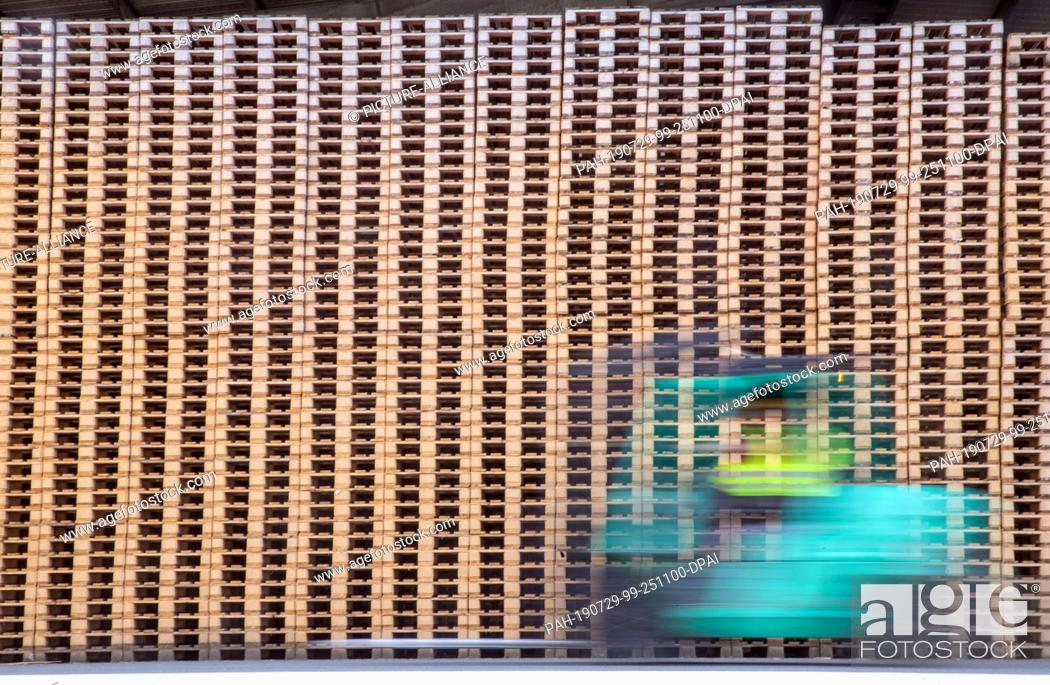 Stock Photo: 24 July 2019, Mecklenburg-Western Pomerania, Wismar: A forklift truck drives past new wooden pallets in the storage area of the company Paletten-Service (motion.