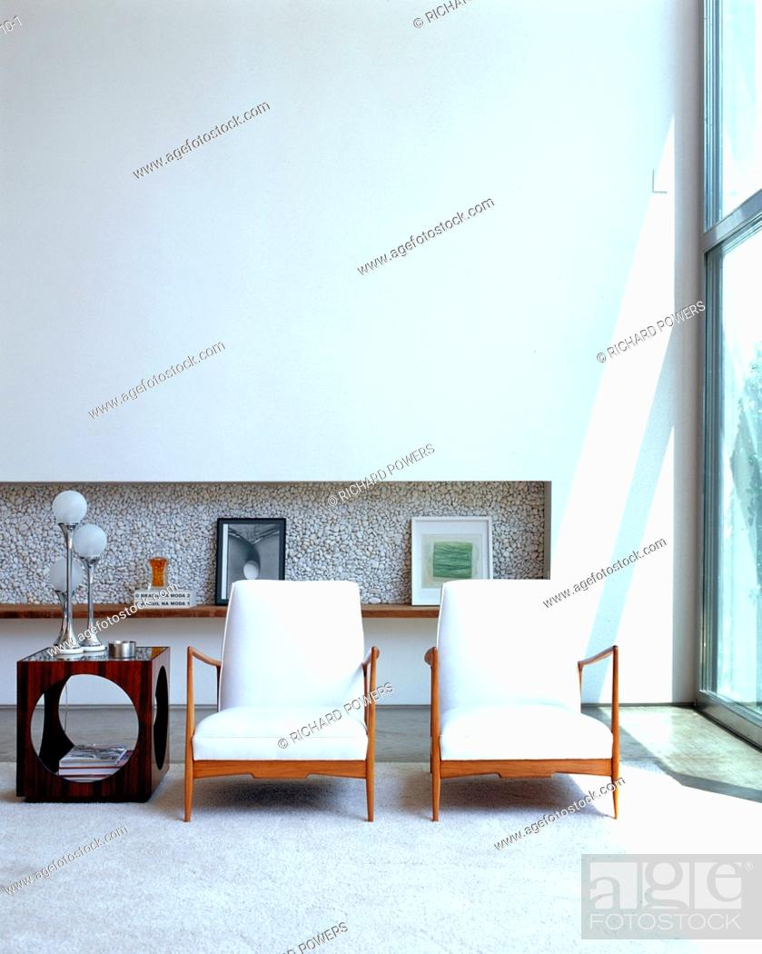 White matching chairs and recessed shelving in living room ...