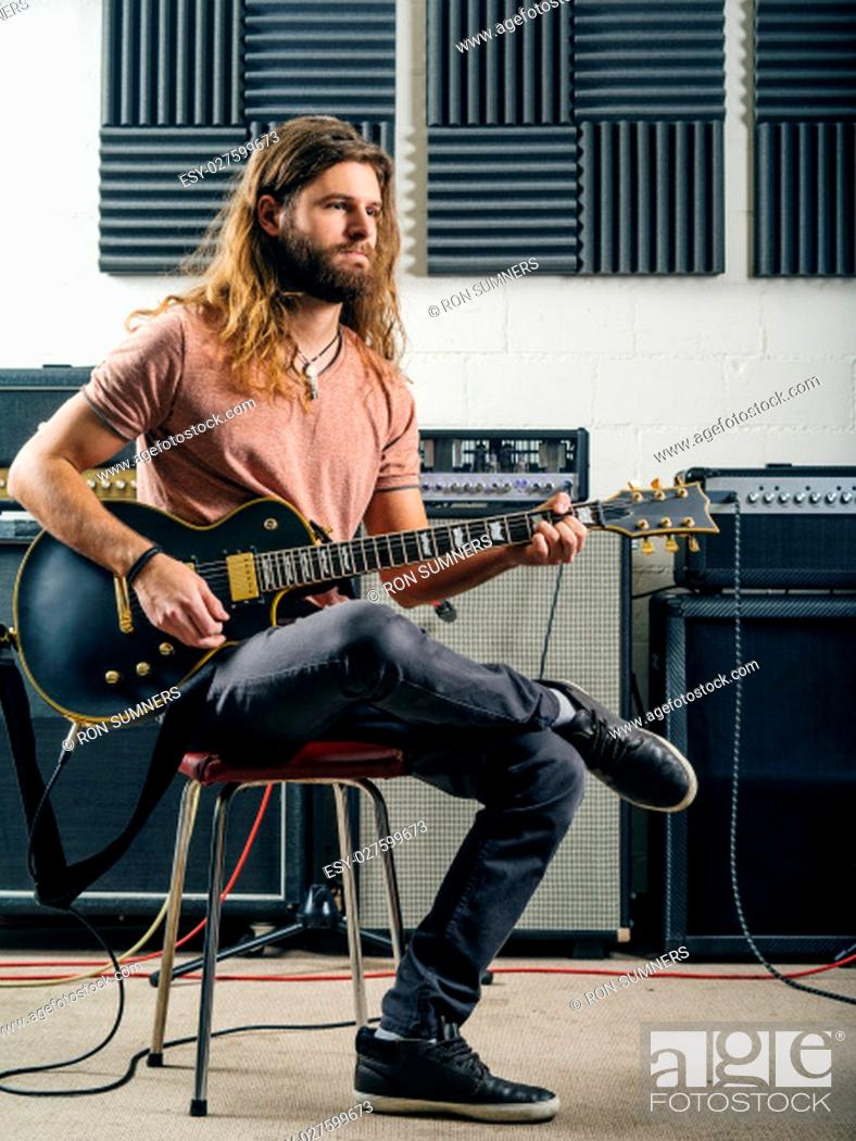 Imagen: Photo of a young man with long hair and beard playing electric guitar in a recording studio.