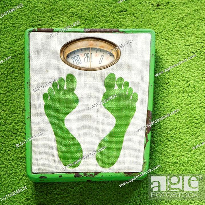 Stock Photo: Vintage foot scale with green footprints against green carpet.