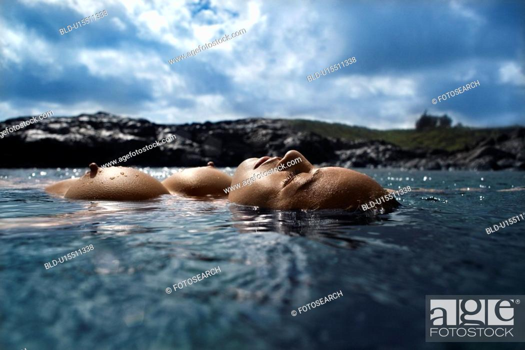 Stock Photo: Young Asian nude woman floating on back on rocky coast.