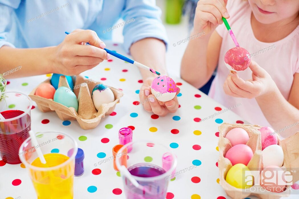Stock Photo: Cropped shot of woman and daughter's hands painting easter eggs at table.