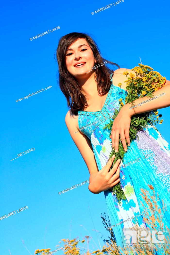 Stock Photo: Young, beautiful girl in a blue dress holding wildflowers and looking up with a smile.