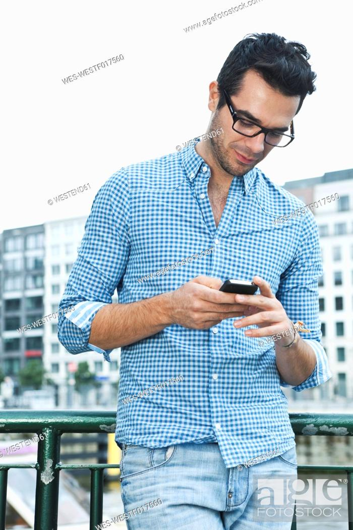 Stock Photo: Germany, Berlin, Man using cell phone in city.