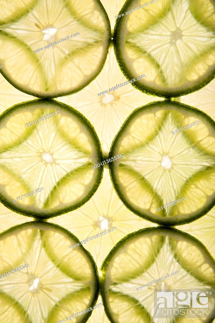 Stock Photo: Lime slices arranged in design on white background.