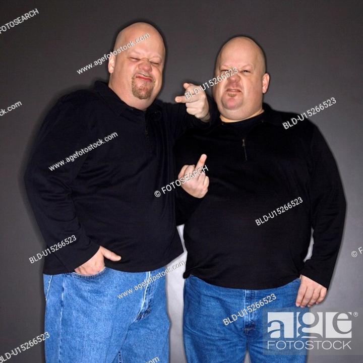 Stock Photo: Bald mid adult identical twin men making obscene gesture at viewer.