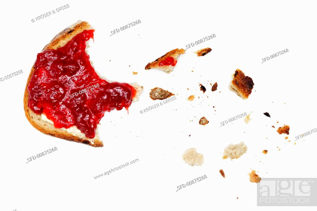 Photo de stock: A slice of bread and jam, partly eaten.