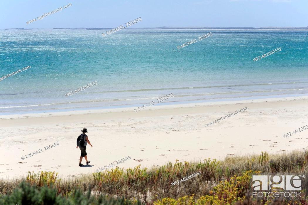 Imagen: Australia, South Australia, Robe, woman walking on the beach.