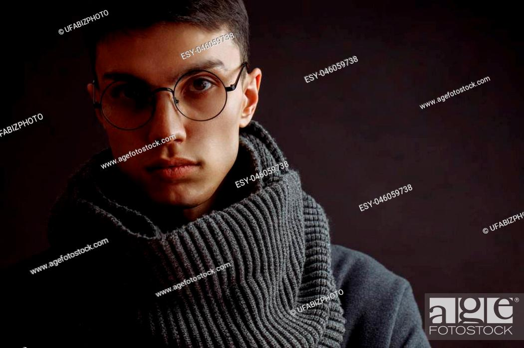 Stock Photo: Portrait of handsome young creative person, painter, artist, man in glasses, wearing winter coat and scarf looking at camera.