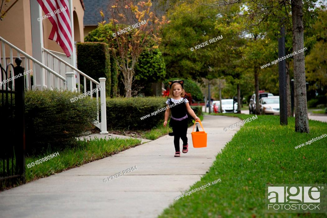 Stock Photo: Girl trick or treating in cat costume walking along sidewalk.