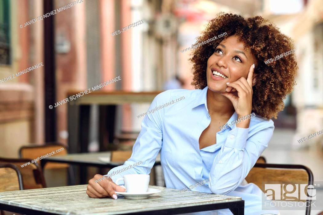 Stock Photo: Smiling woman with afro hairstyle sitting in outdoor cafe.