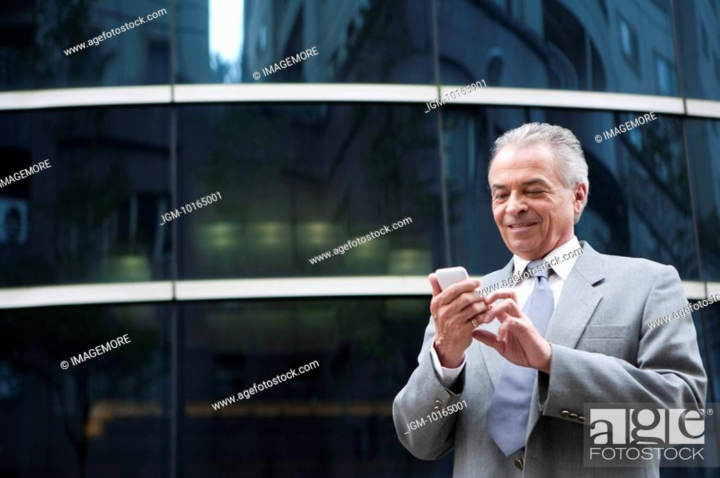 Stock Photo: Senior Businessman holding mobile phone in front of an office building.