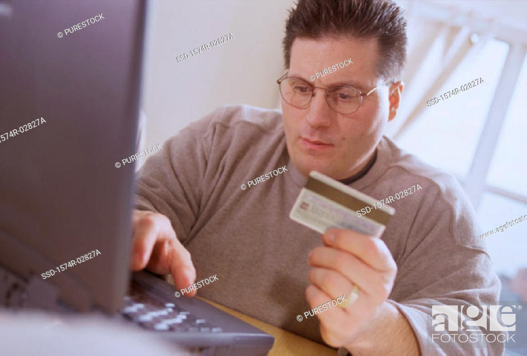 Stock Photo: Young man sitting in front of a laptop holding a credit card.