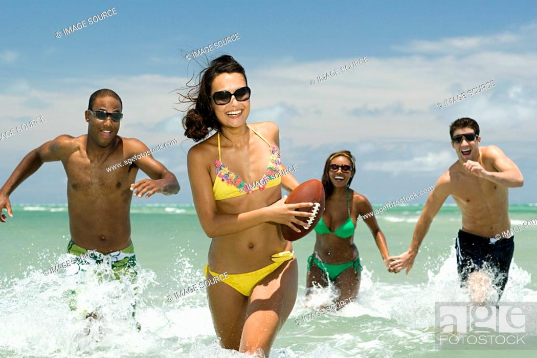 Stock Photo: Friends running in sea with football.