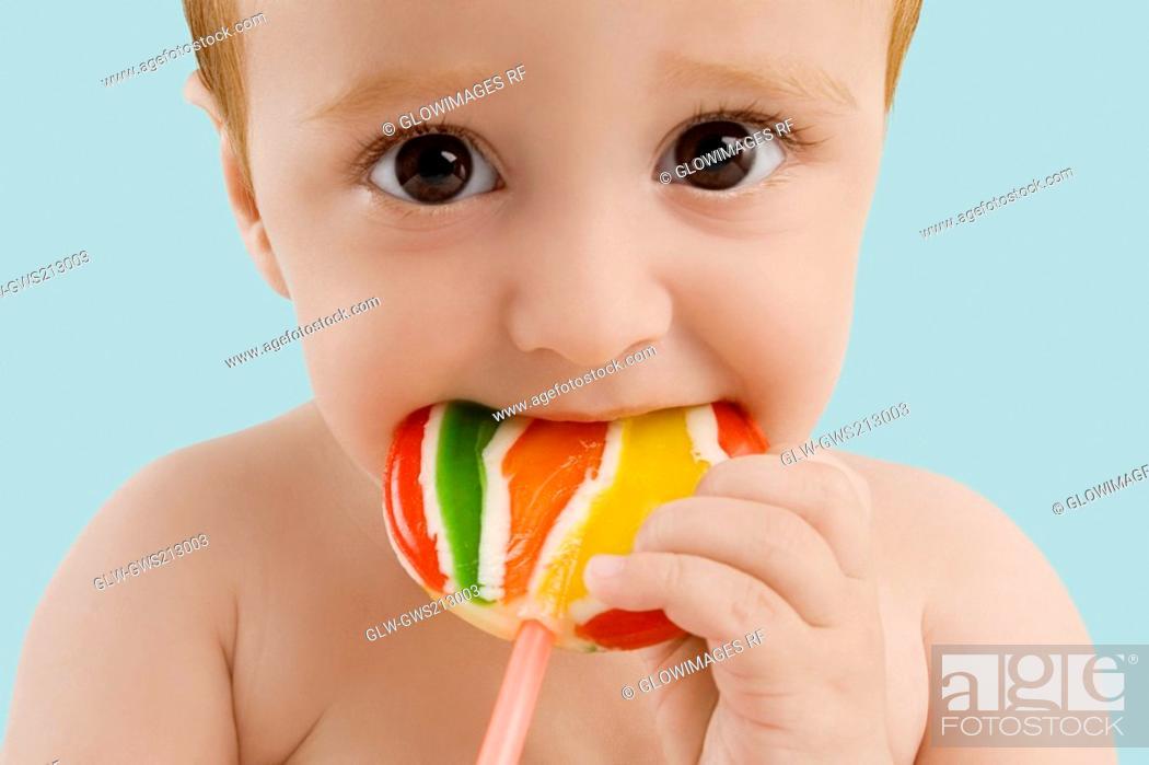 Stock Photo: Portrait of a boy licking a lollipop.